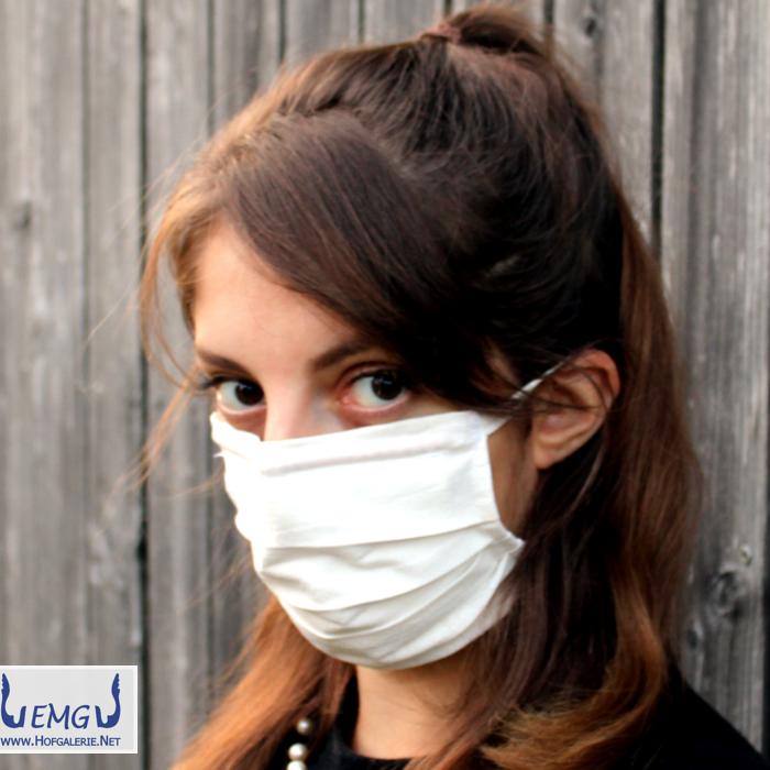 Behelfs-Mund-Nasen-Maske weiß, mit Bändern. Das obere Band ist waagerecht um den Kopf geführt. - Halbprofil