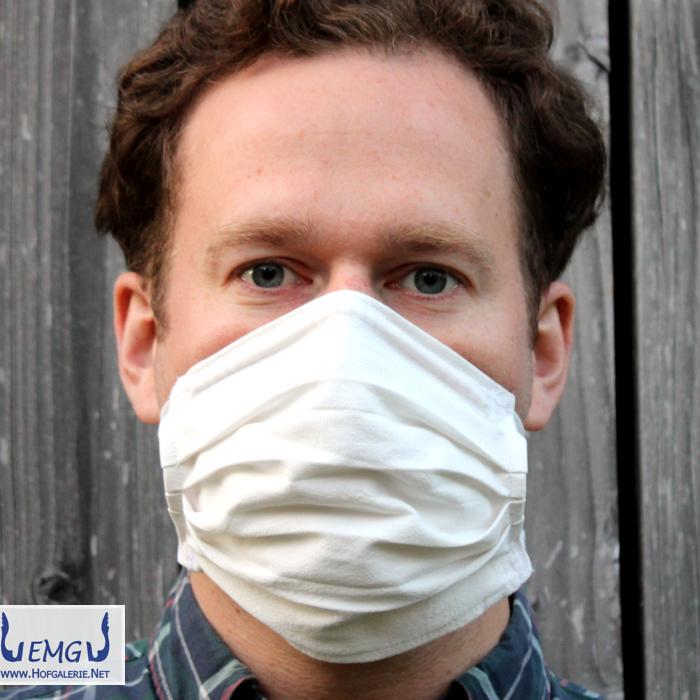 Behelfs-Mund-Nasen-Maske weiß, mit Bändern. Das obere Band ist diagonal um den Kopf geführt und im Nacken zusammengebunden. Es geht auch anders, aber so geht es auch. - Sicht von vorn.