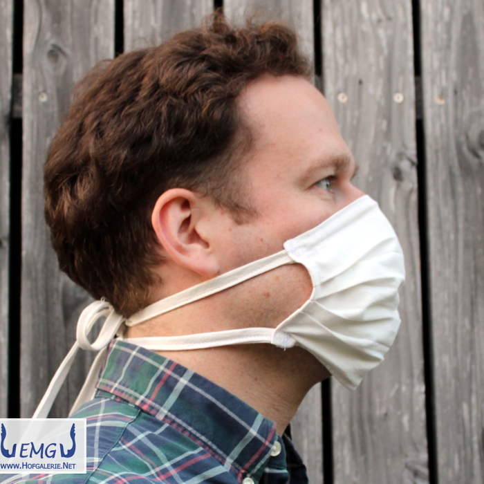 Profil: Behelfs-Mund-Nasen-Maske weiß, mit Bändern. Das obere Band ist diagonal um den Kopf geführt und im Nacken zusammengebunden. Es geht auch anders, aber so geht es auch.